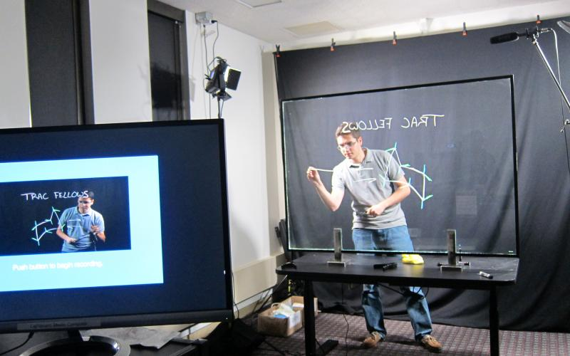 One Button Studio student behind lightboard with rendering on PC